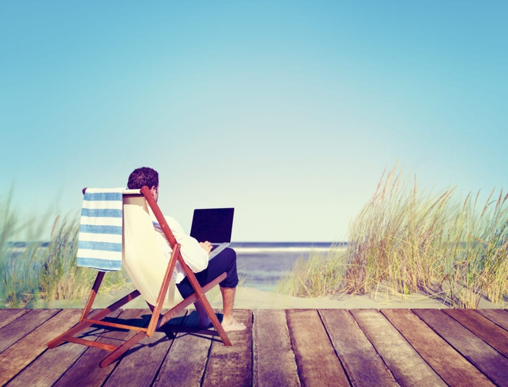 man working remotely at beach