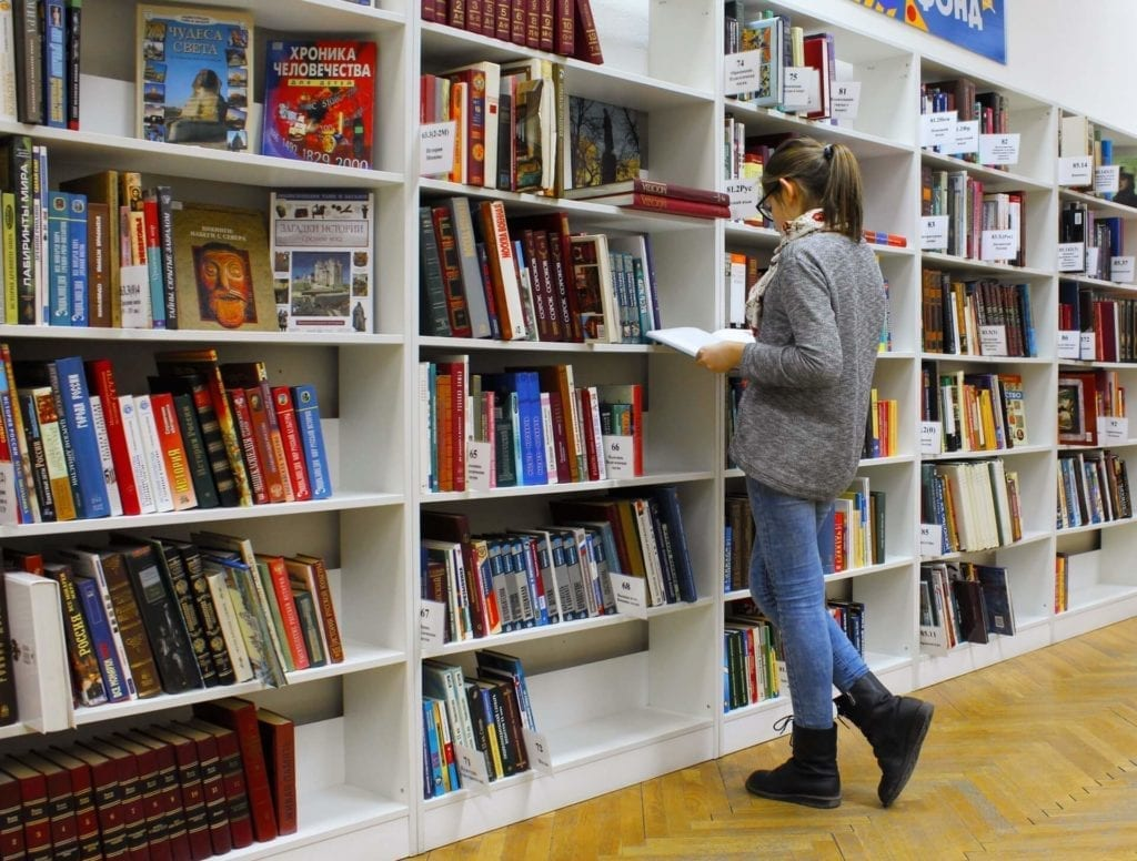 Female in library looking through books on a shelf