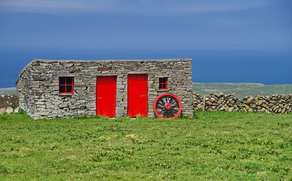 Old Irish stone cottage with red door and windows